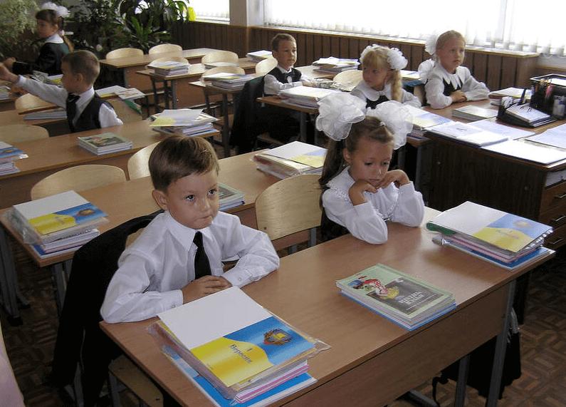 На фото изображены первоклассники, которые сидят за партами в классе.