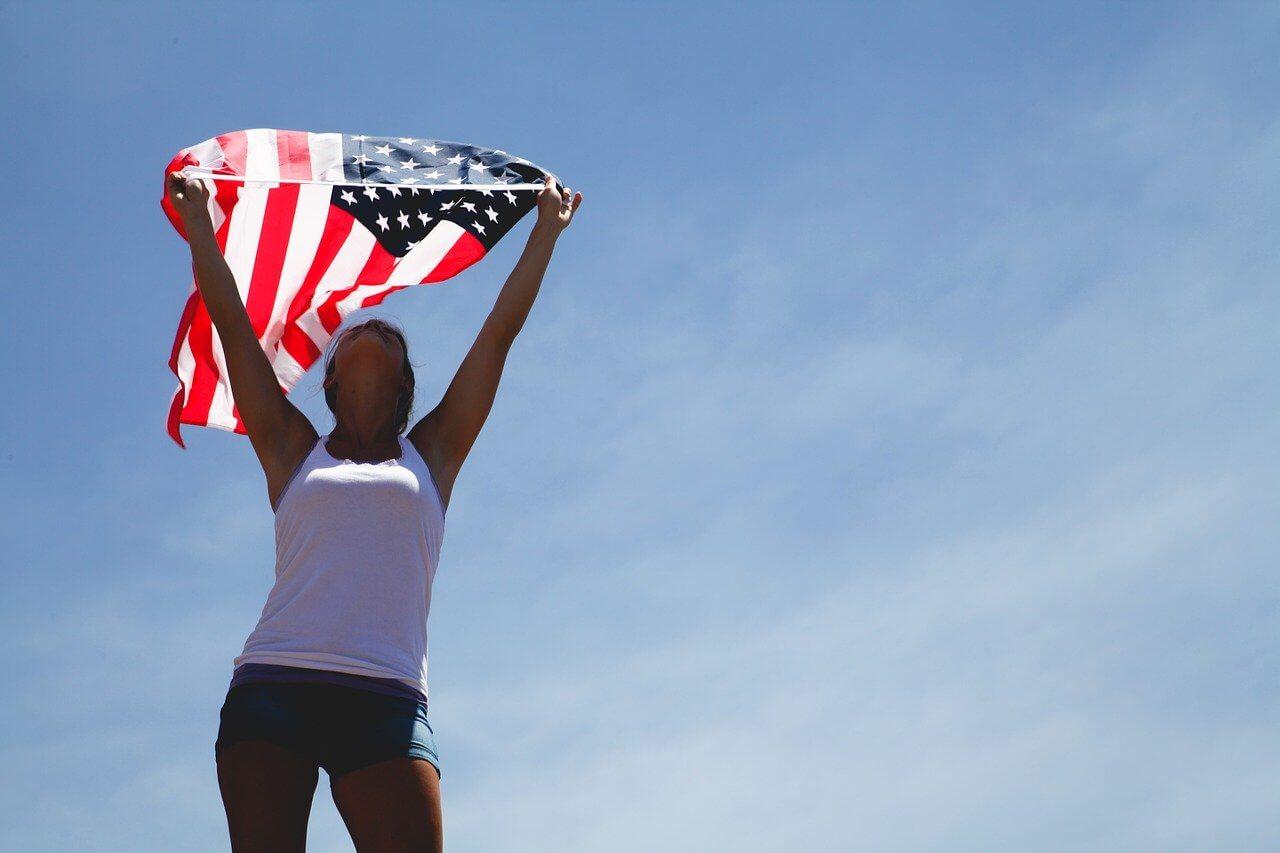 На фото изображена девушка с флагом США.