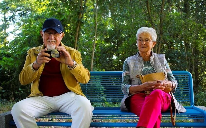 На фото изображены пенсионеры на лавочке.