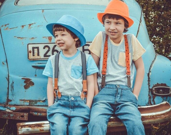 Два брата сидят на старой машине.