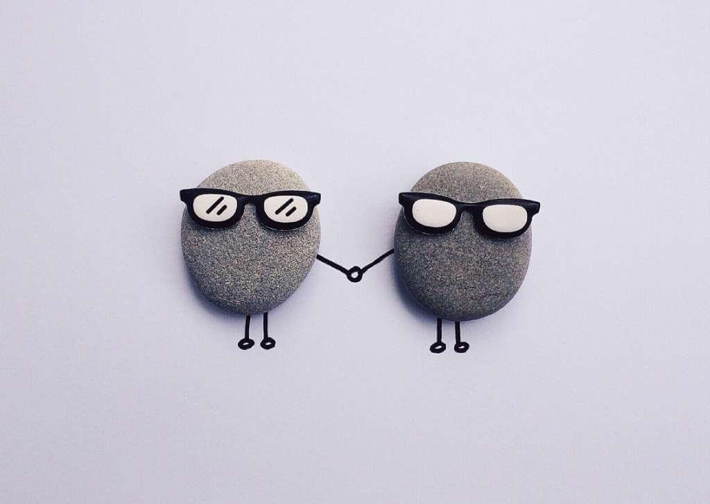 На фото два камня держатся за руки.