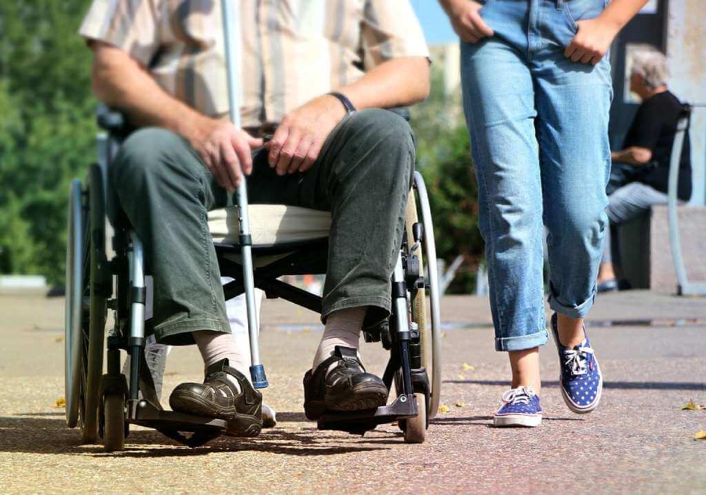 На фото изображен мужчина в инвалидной коляске.