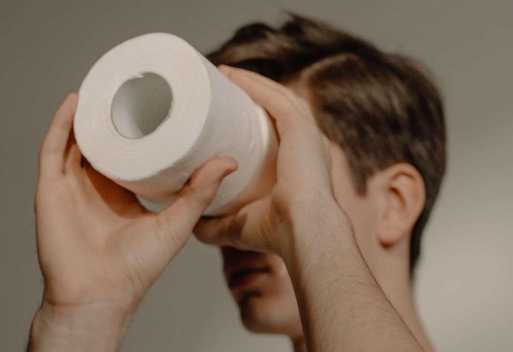 На фото изображен парень с рулоном туалетной бумаги.