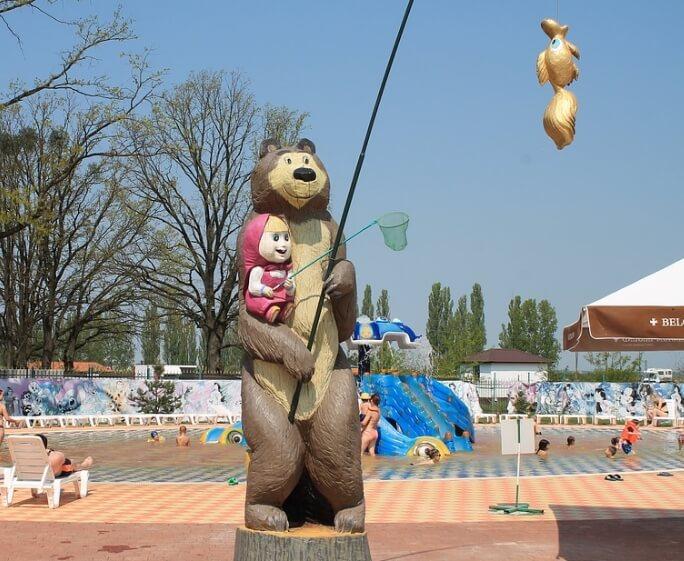 Маша и медведь ловят рыбу.