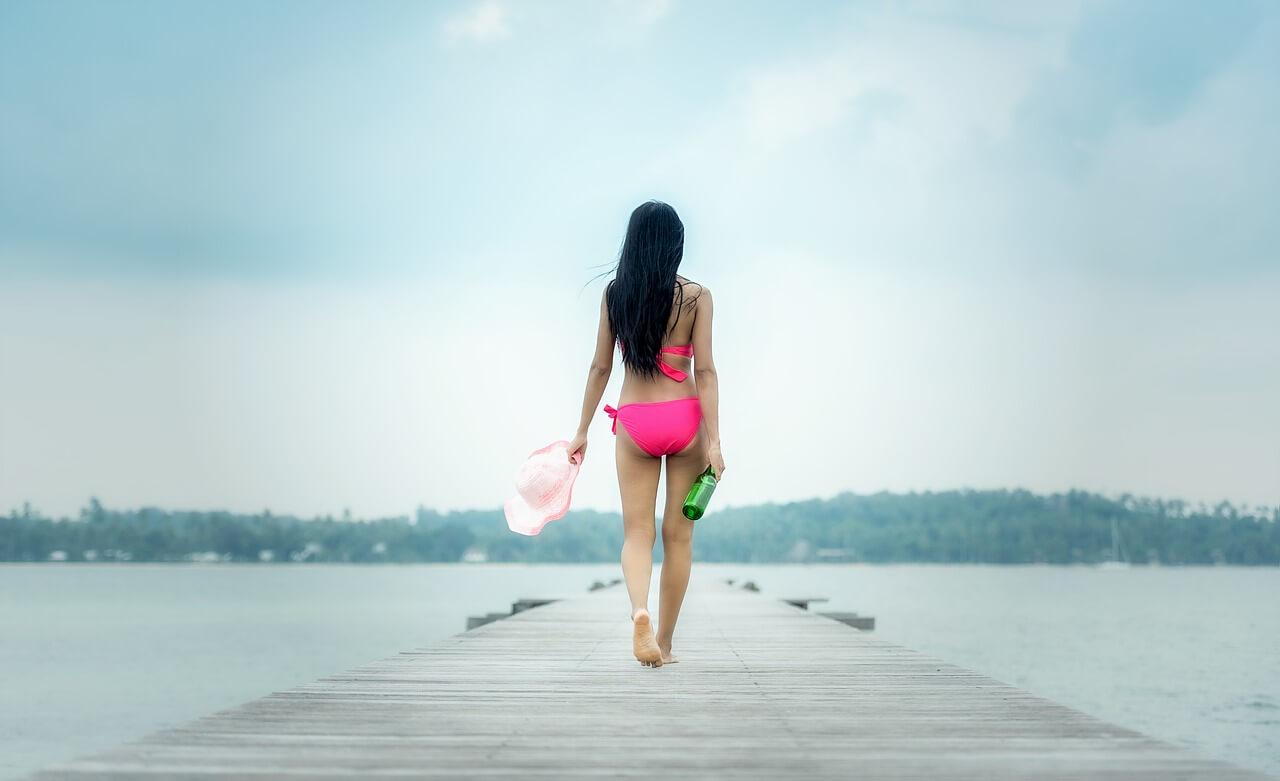 На фото девушка в купальнике с бутылкой алкоголя в руке.