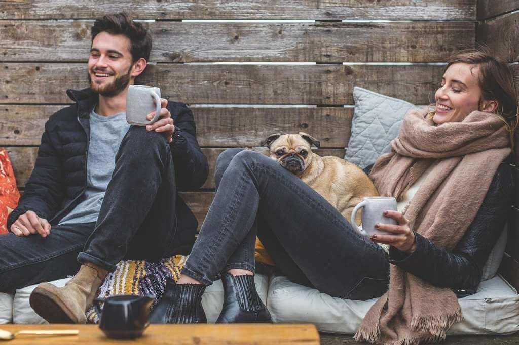 На фото изображена счастливая пара и собачка.