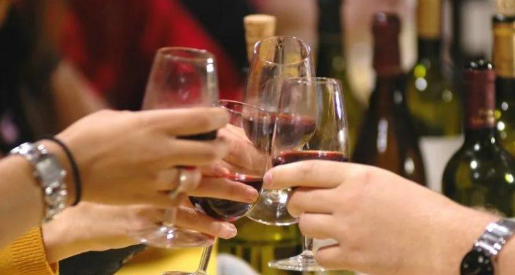 Гости собрались за столом и цокаются бокалами. Произносят тосты на юбилей.